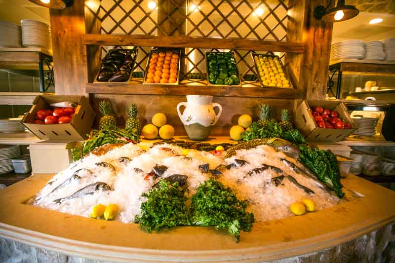 Estia Taverna kitchen area with bread, fish, and fresh produce displays